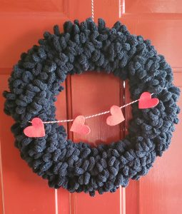 black yarn wreath on red door